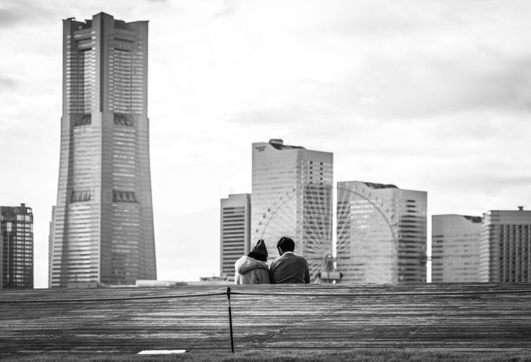 Rear View Of Couple Sitting By Retaining Wall Against Cityscape