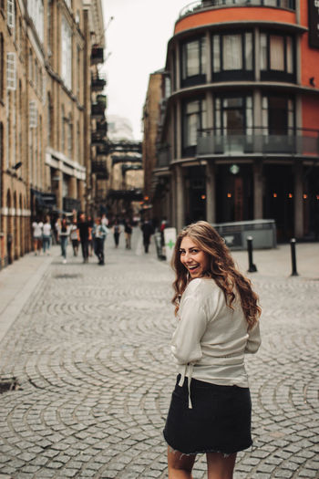 Portrait of smiling woman on street in city