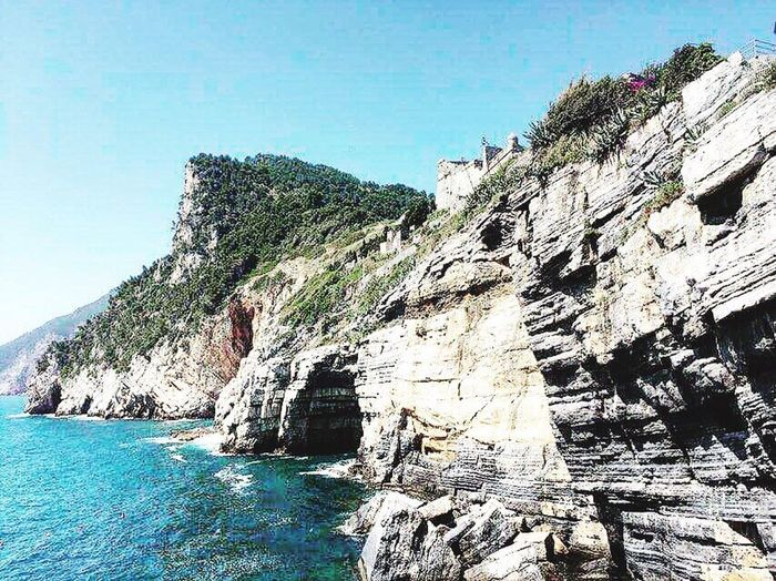 Rock - Object Sea Blue Scenics Cliff Real People Clear Sky Nature Geology Day Water Full Length Beauty In Nature Adventure Leisure Activity Outdoors Vacations Italy Tuscany Portovenere Rock Face