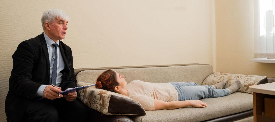 Full length of man holding woman sitting on sofa