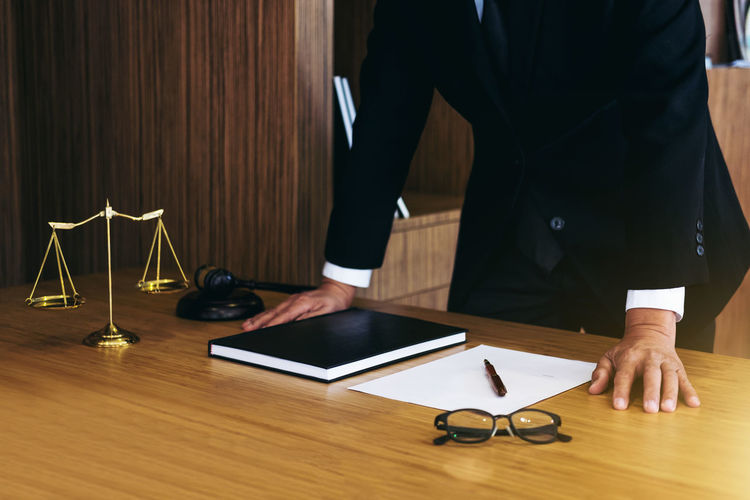 Midsection Of Lawyer Standing By Table