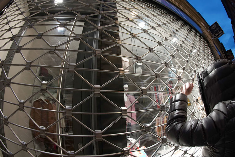 Low angle view of man photographing through metal structure