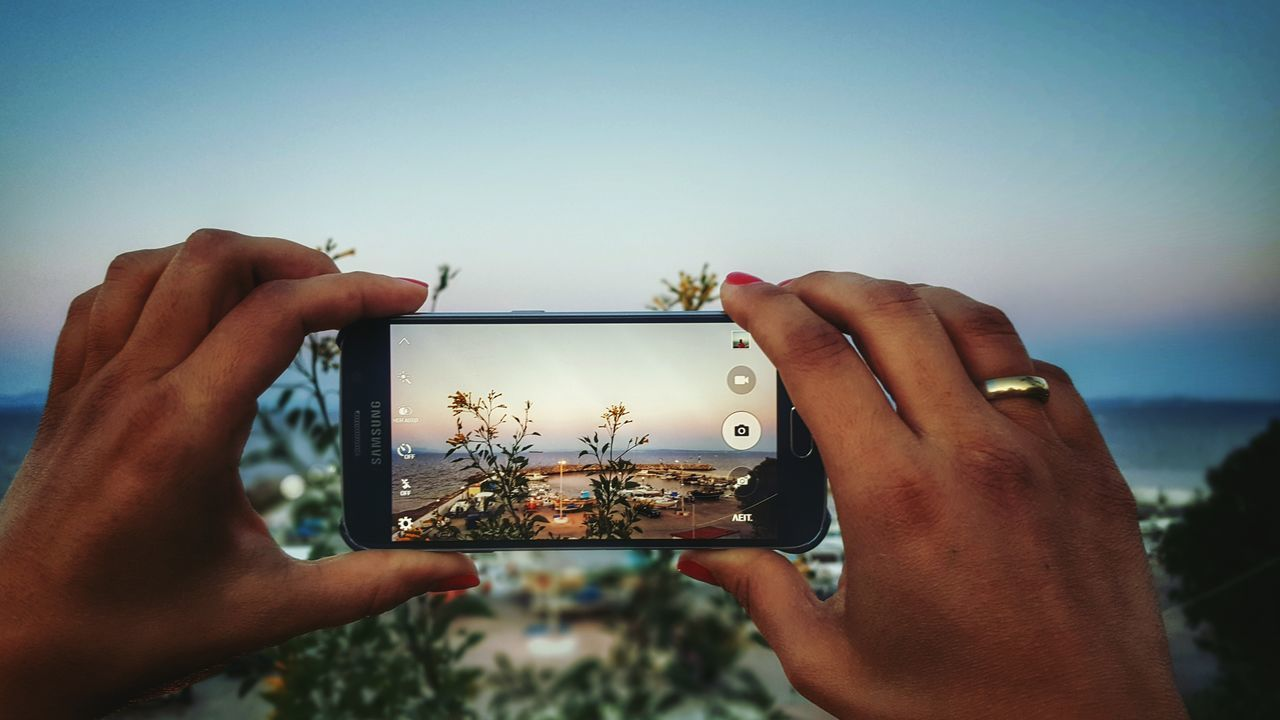 personal perspective, holding, human hand, real people, sky, outdoors, photography themes, clear sky, photographing, leisure activity, nature, sea, togetherness, beach, close-up, sunset, wireless technology, leisure, day, people