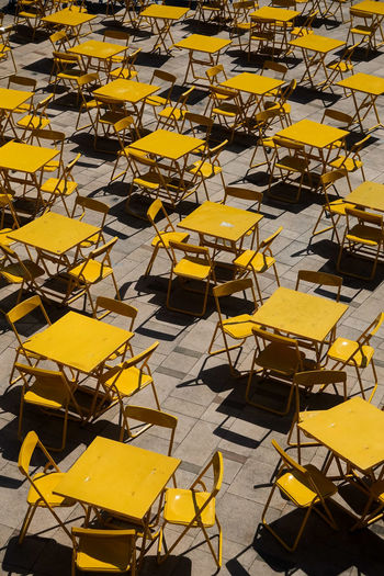 High angle view of empty chairs and table outdoors