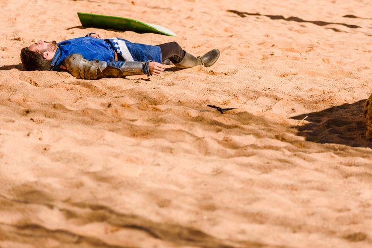 Boy sleeping on sand