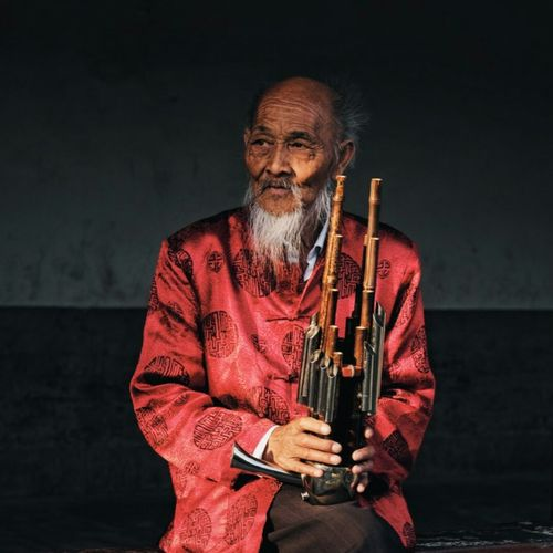 Senior Man Holding Musical Instrument While Sitting Against Wall
