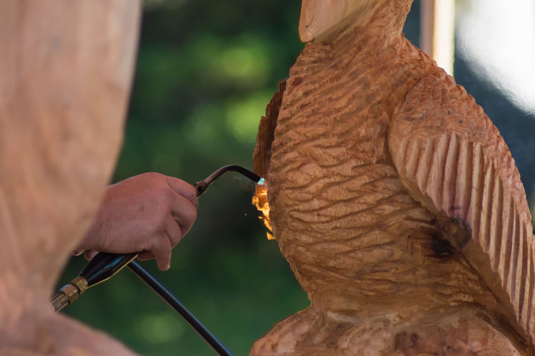 Cropped image of man using blow torch on wooden sculpture