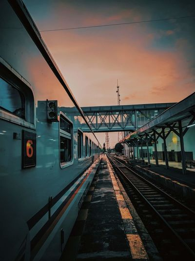 Train at railroad station against sky during sunset