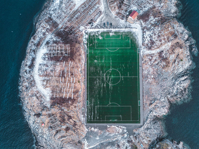 Henningsvær is a village in the Lofoten Islands hosting about 500 people. The peculiarity of this place is its soccer field with synthetic grass surrounded by the sea water, called Henningsvaer stadion. Photo taken with a drone. Communication Water Green Color Architecture Day No People Blackboard  Text Outdoors Nature Sea Built Structure Building Number Sport Activity Board Norway Henningsvaer Henningsvær Football Football Stadium Stadium Soccer Soccer Field First Eyeem Photo 2018 In One Photograph