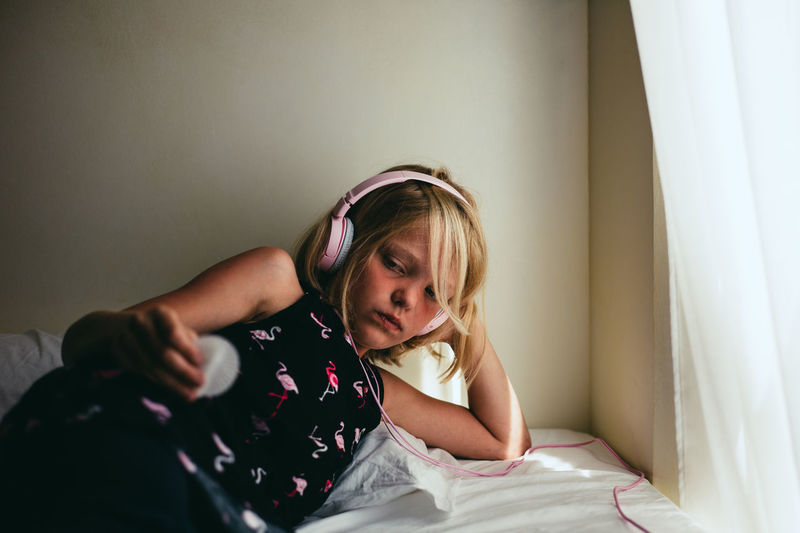 Girl wearing headphones while lying on bed at home