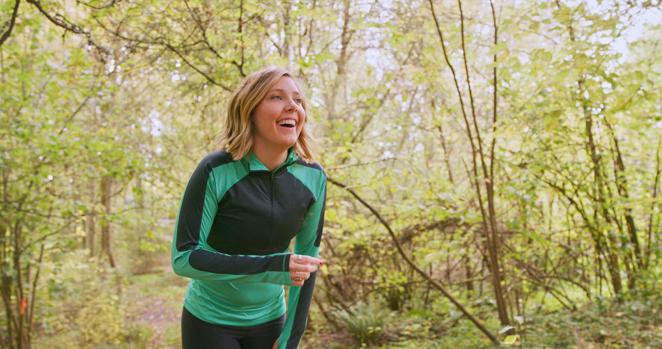 Smiling young woman exercising in forest