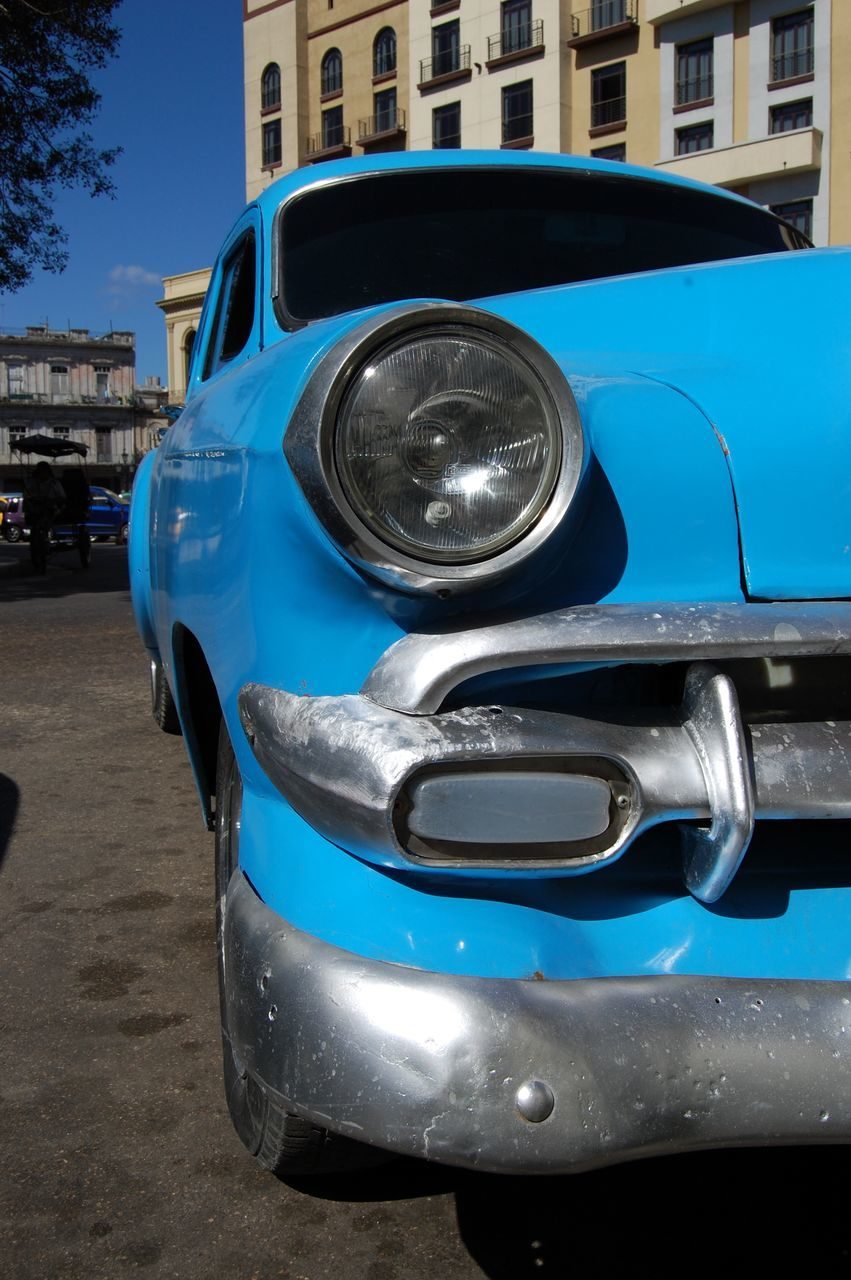 Close-Up Of Blue Car Parked On Street
