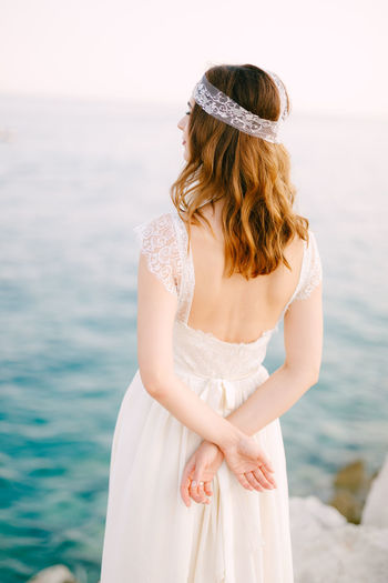 Rear view of bride looking at sea against sky