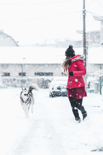 Snow Real People Winter Cold Temperature One Person Mammal Lifestyles Warm Clothing Domestic Full Length One Animal Clothing Domestic Animals Leisure Activity Pets Women Snowing Outdoors Extreme Weather Husky