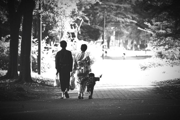 Rear view of people walking on road in park