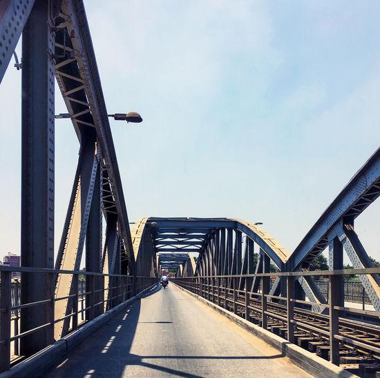 Bridge over road in city against sky
