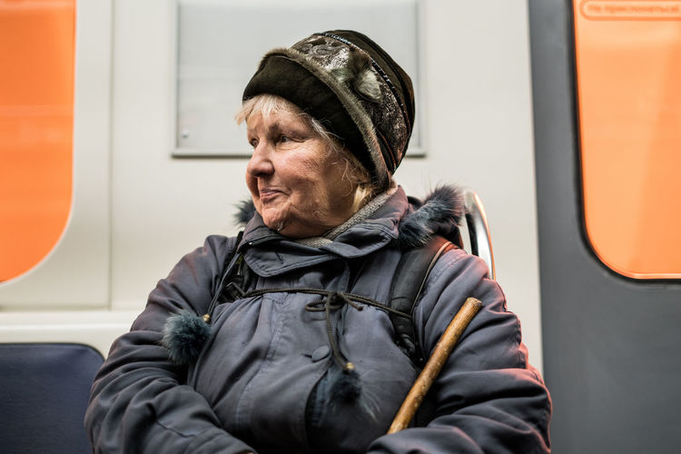 Public Transportation One Person Clothing Real People Senior Adult Mode Of Transportation Transportation Sitting Lifestyles Adult Train Travel Train - Vehicle Vehicle Interior Rail Transportation Passenger Warm Clothing Jacket Portrait Subway Train