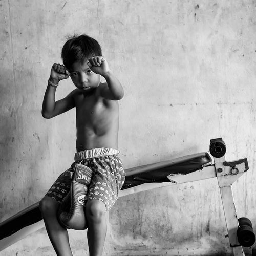 Small boy poses for portrait in family gym in Southern Thailand Documentary Photography MuayThai