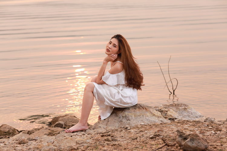 Young woman sitting on rock at beach during sunset