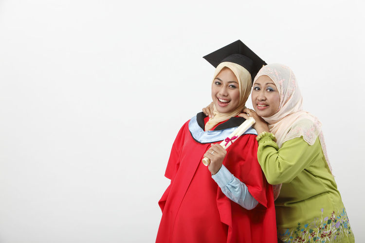 mother celebrate with her daughter's graduation Achievement Celebration Graduation Happiness Isolated Mother And Daughter Muslimah Proud Mommy Beautiful Woman Copy Space Education Graduation Gown Headwear Malay Ethnicity Mortarboard Portrait Positive Emotion Scarf Smiling Studio Shot Success Tudung Two People University Student White Background