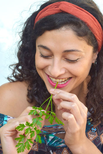 Close-up of smiling young woman eating cilantro