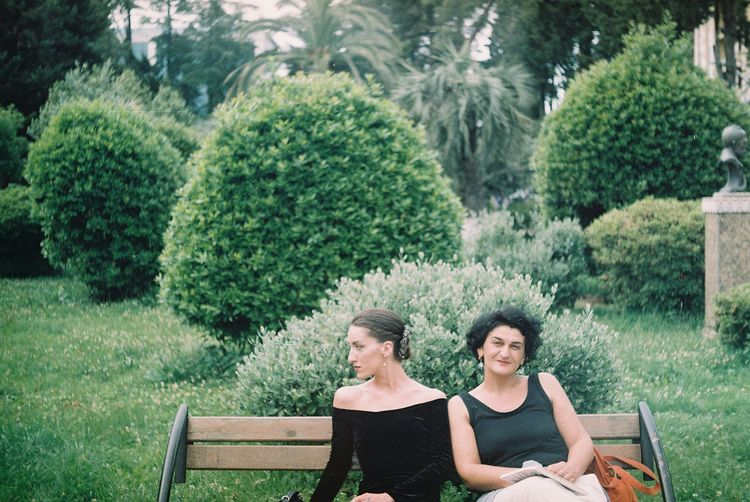 Smiling woman sitting by disappointed friend on bench at park