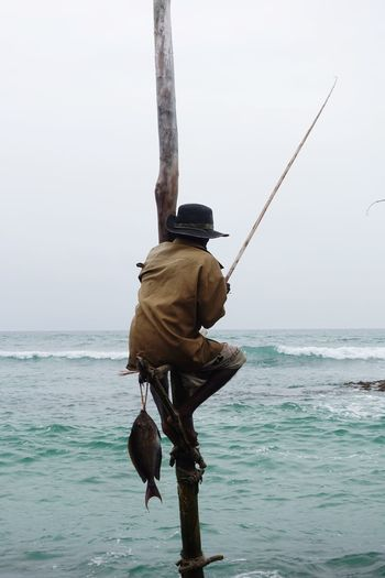 Rear view of man fishing in sea while sitting on bamboo against sky