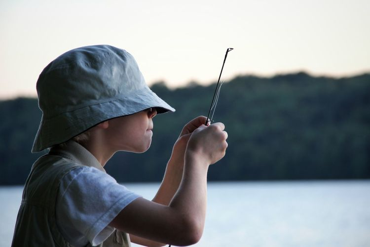 Side View Of Boy Holding Stick Against Lake