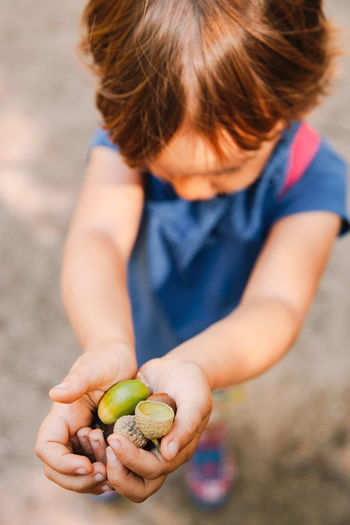 High angle view of girl holding fruit