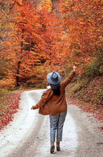 Rear view of woman on path in forest, fall colors, autumn, style, influencer.