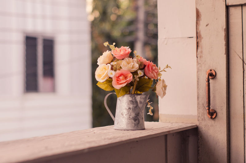 Close-up of flower vase on window of building