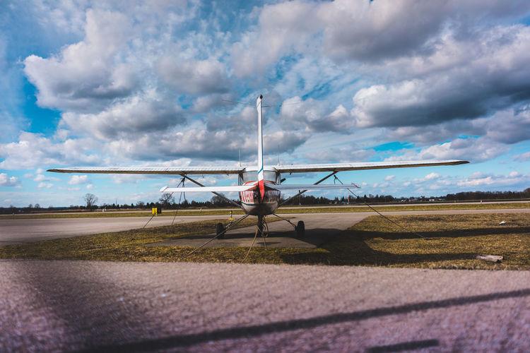 Biplane on runway against cloudy sky