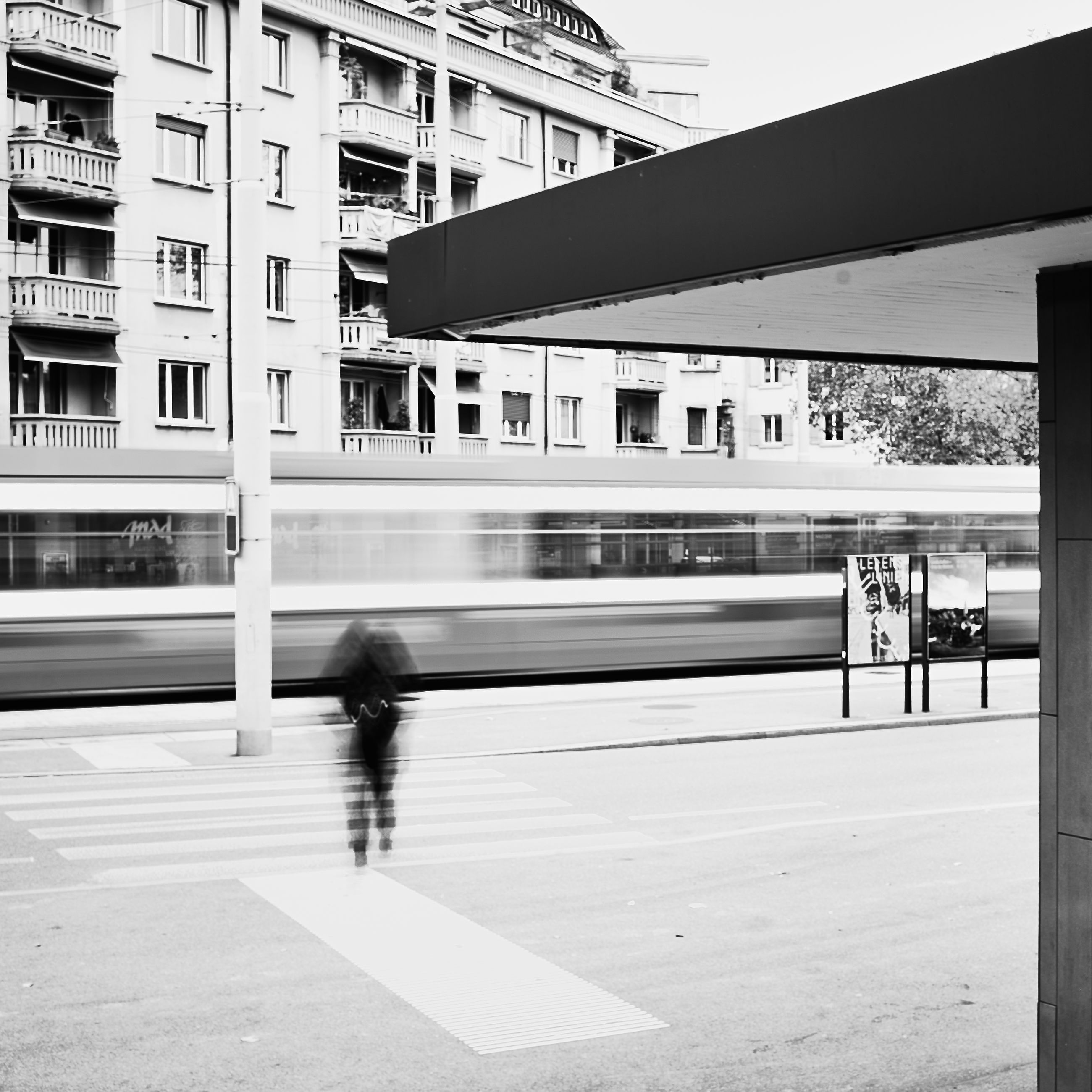 architecture, city, transportation, built structure, white, black and white, building exterior, monochrome, monochrome photography, motion, mode of transportation, city life, black, adult, public transportation, day, rail transportation, walking, street, one person, on the move, travel, women, lifestyles, men, road, blurred motion, outdoors, building, railroad station, urban area, railroad station platform, nature