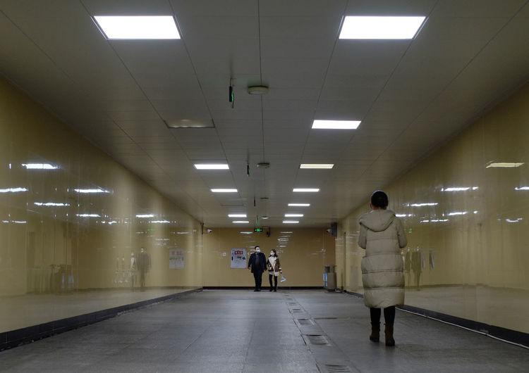 Rear view of people walking in illuminated corridor