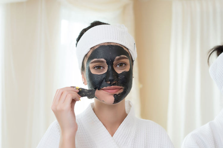 Young woman removing facial mask from face in spa