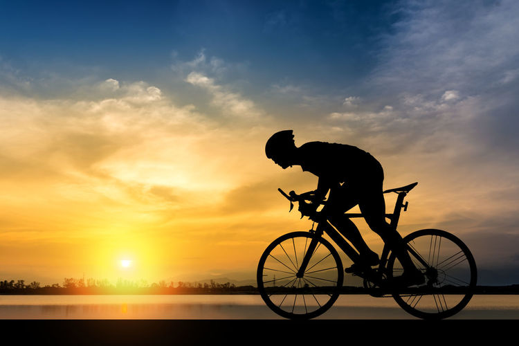 Silhouette of cyclist on the background of beautiful sunset,Silhouette of man ride a bicycle in sunset background. Athlete Exercise Road Weekend Active Activity Bicycle Bike Cycling Health Helmet Lifestyles Men Outdoor Outdoors Ride River Safety Silhouette Sky Sport Strong Sun Sunset Water