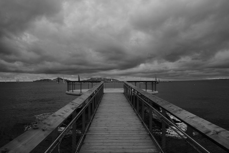 Pier in sea against cloudy sky