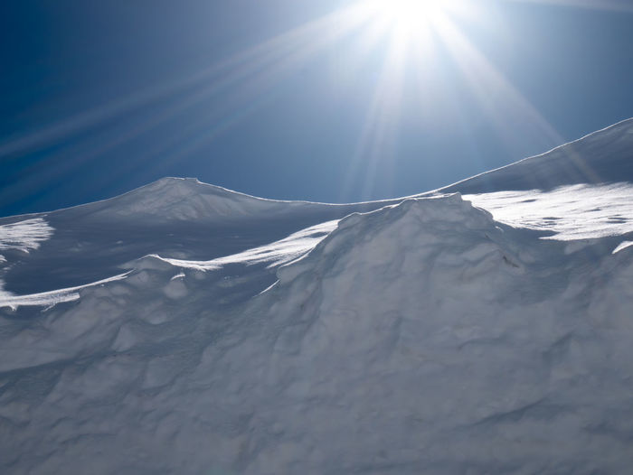 Scenic view of snowcapped mountains against sky on sunny day