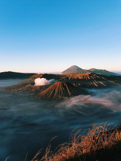 Scenic view of volcanoes against clear blue sky