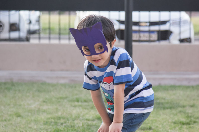 Portrait of boy wearing eye mask on field