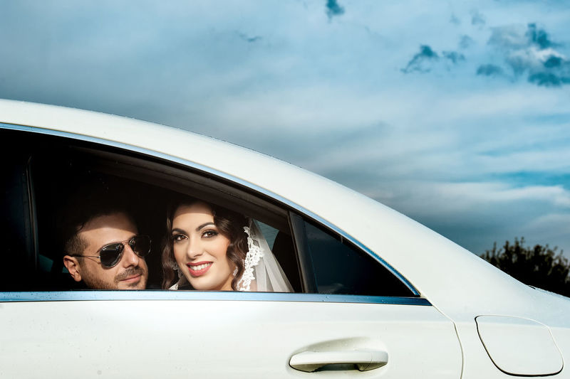 Adult Car Cloud - Sky Couple - Relationship Fashion Happiness Headshot Land Vehicle Men Mode Of Transportation Motor Vehicle Outdoors Portrait Real People Road Trip Smiling Togetherness Transportation Travel Two People Women Young Adult Young Men Young Women