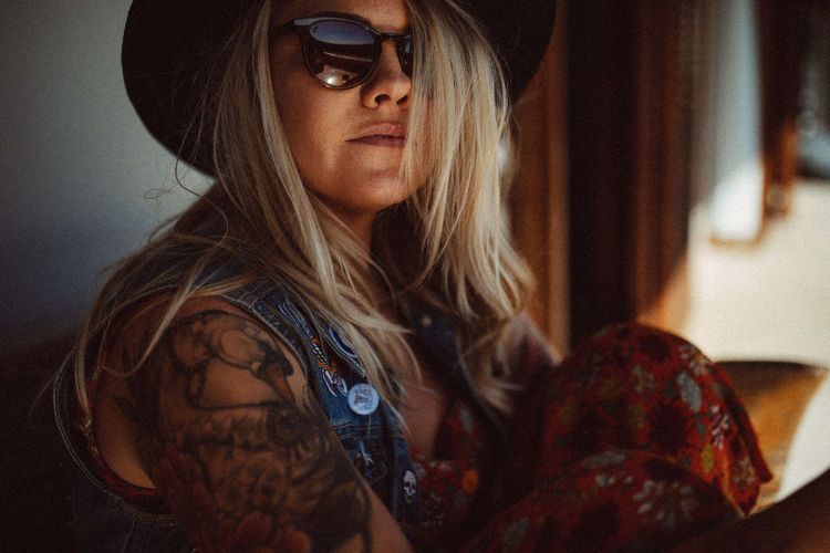 Close-Up Portrait Of Serious Tattooed Woman Wearing Hat At Home
