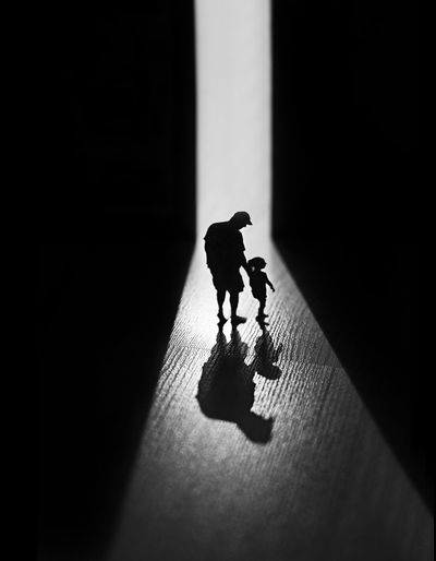 Silhouette people with toy standing on floor