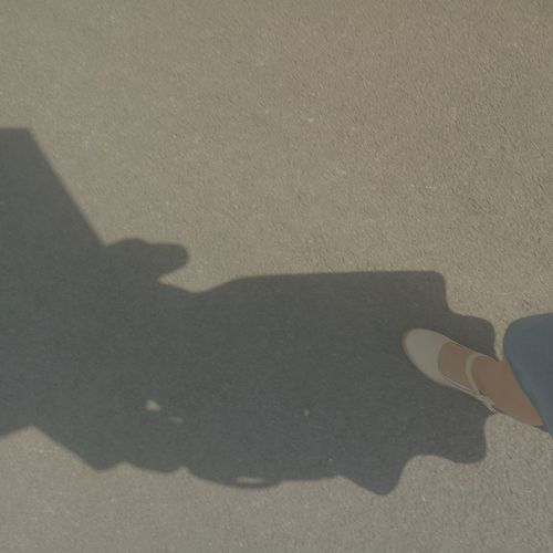 The Sun An Umbrella With A Girl Leather Shoes Walking Around