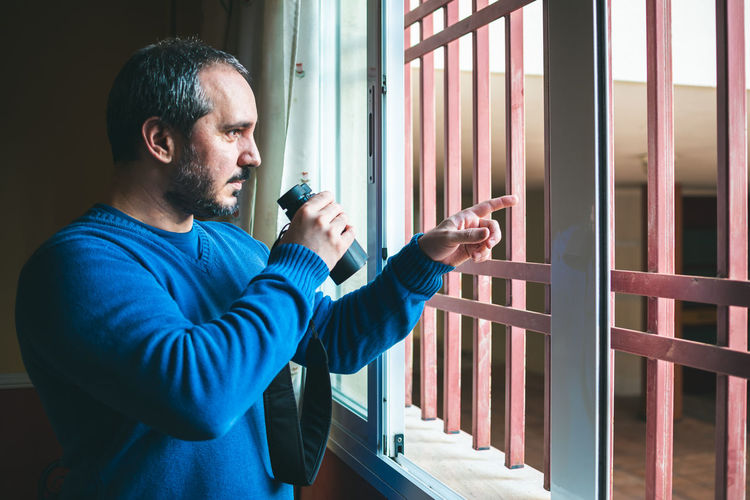 Man with binoculars standing by window at home