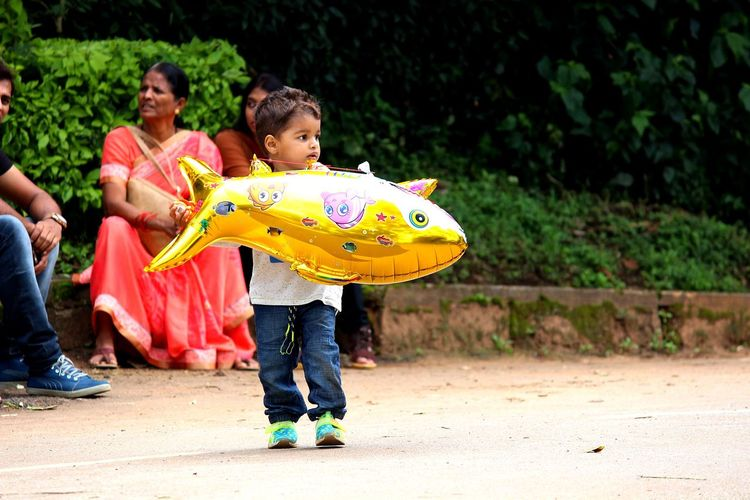 Cute Boy Holding Balloon With Parents Sitting In Background At Park
