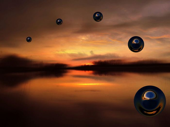 Digital composite image of bubbles over lake against cloudy sky during sunset