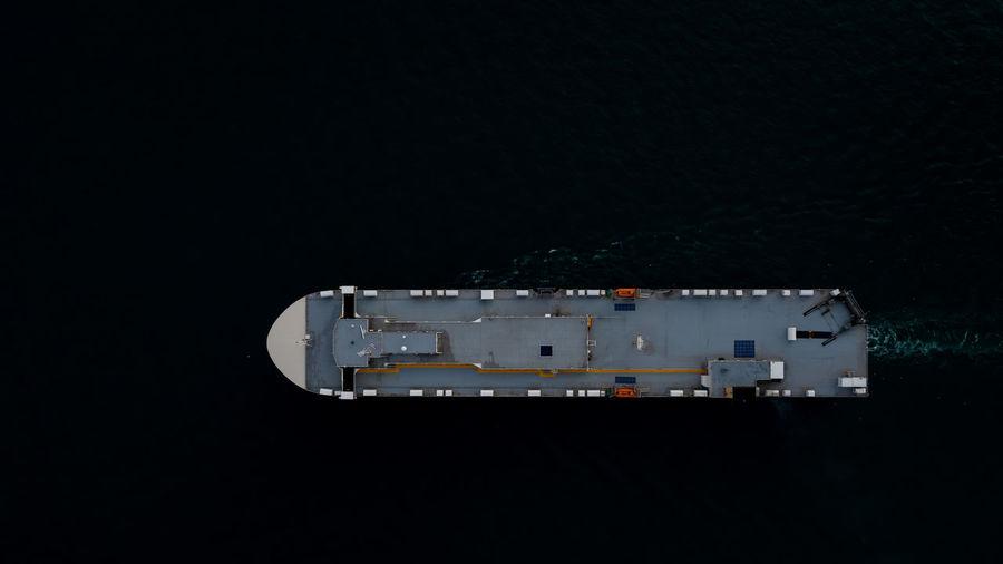 Roro ship sailing in the dark sea aerial top view transportation international concept