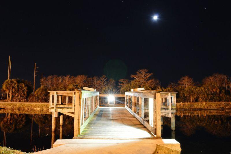 Illuminated scene of wooden bridge at night