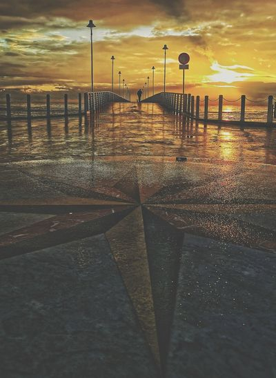 Surface level of wet street against sky during sunset
